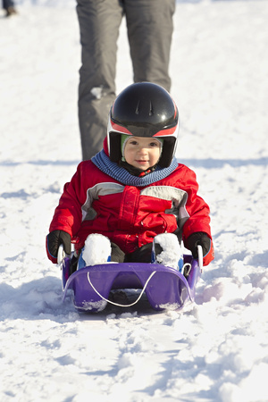 bobsled: cute little boy descended the hill bobsledding Stock Photo