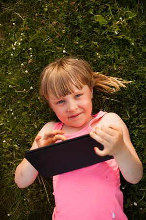 girl lying down: Little blond girl lying down playing with a tablet. Stock Photo