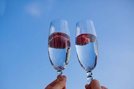 sektglas: Gläser Champagner und Erdbeeren mit einem Hintergrund des blauen Himmels.