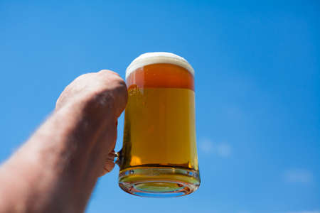 contra: Closeup of a glass of beer contra a blue sky. Stock Photo