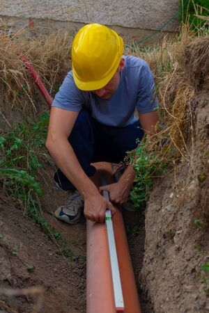 culvert: Worker at connecting sewer pipes to measure the slope of the pipe (Shallow DOF).