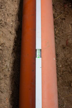pipework: View of sewer pipes in the construction of household sewer with spirit level (Shallow DOF).