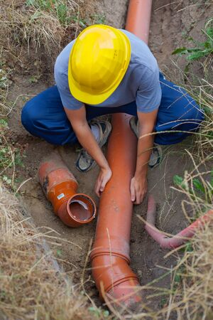 Worker at connecting sewer pipes (Shallow DOF).