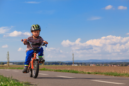 helmet bike: Little boy on a bicycle for the first time. Stock Photo