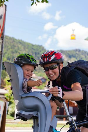 child seat: Mother and son on a cycling trip using safety devices (helmets, child seat). Shallow DOF.