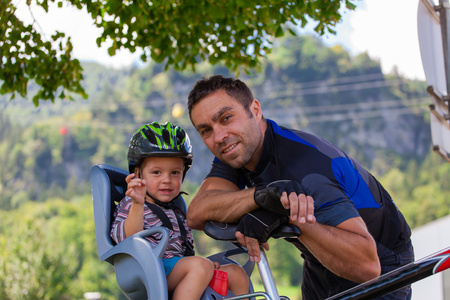 child seat: Father and son on a cycling trip using safety devices (helmets, child seat). Shallow DOF.