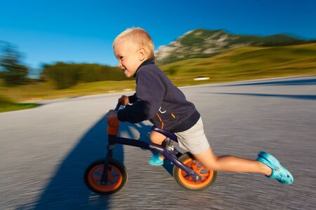 Little boy riding fast on a bicycle (Motion blurred; shallow DOF). Stock Photo