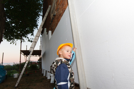 roof framing: Little boy helps in building insulation polystyrene (reconstruction of the house). Stock Photo