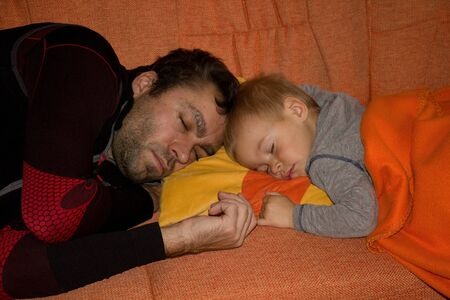 cradling: The little boy sleeping with his father. Stock Photo