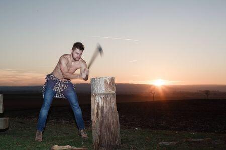 hatchet man: The stylish lumberjack chopping wood at sunset. (Motion blur axe).