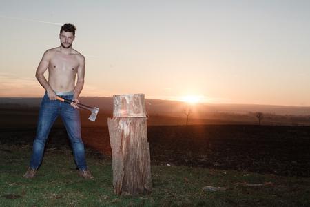 lumberjack shirt: The stylish lumberjack chopping wood at sunset. Stock Photo
