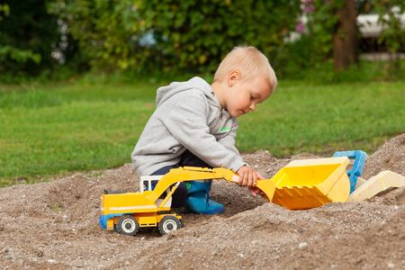 little colours: Little boy playing with children excavator in the sandbox. Stock Photo