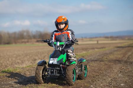 A little boy rides his electric ATV quad.