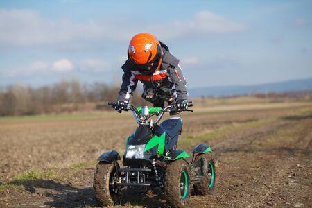 atv: A little boy rides his electric ATV quad.