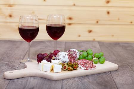 bebiendo vino: Queso y carne con vasos de vino tinto. Foto de archivo