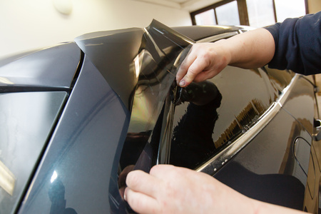tinting: Applying tinting foil on a car window in a garage