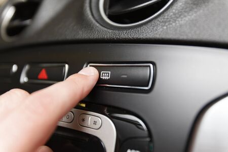 recirculate: Man pressing button defrost (Shallow DOF). Stock Photo