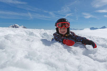 Cute little skier resting while skiing in the Austrian Alps.