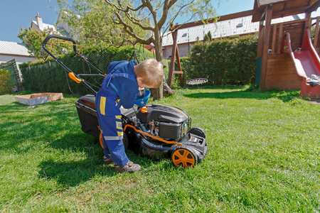 mows: Cute, little boy mows the lawn. Boy inspects the mower, before driving or left engine oil.