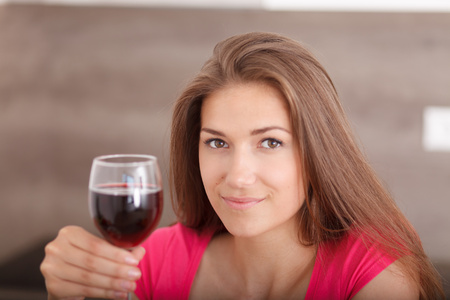 deliberately: Beautiful, young, smiling woman toasting to health. Young girl with red wine. Deliberately focused on her right eye (Shallow DOF).