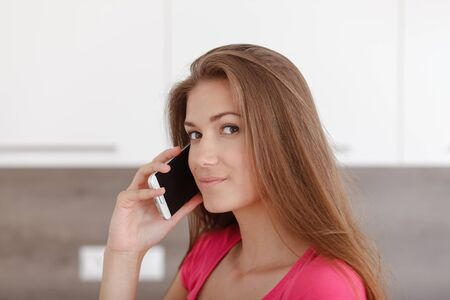 communicates: Pretty young girl communicates using a a mobile phone. Pretty woman calling by phone with her friends. Stock Photo
