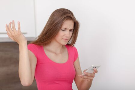 disturbing: Beautiful young girl communicates via a mobile phone. Receives a disturbing message. He feels angrily.