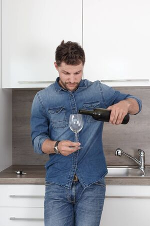 romantic man: Portrait of a confident man in a denim shirt. Man in modern kitchen pouring red wine into a glass.