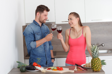likeable: Young couple, man and woman celebrating the new modern kitchen. Beautiful girl and likeable boy with a glass of red wine.