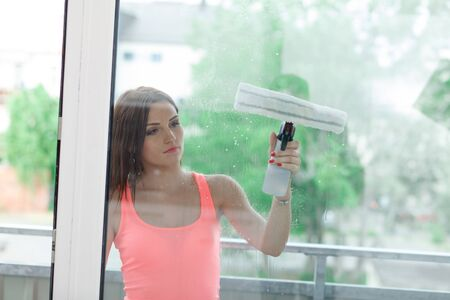homemaker: Beautiful young woman cleans a home. The girl washes the windows with a squeegee. Stock Photo