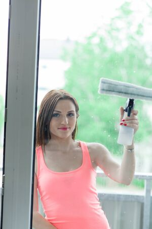 Beautiful young woman cleans a home. The girl washes the windows with a squeegee. Stock Photo