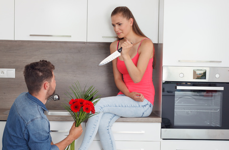 threatens: Man asks for the hand of a woman at the wrong time. Woman disagrees and threatens boyfriend with a knife.