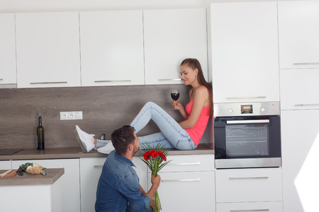 Man asks for the hand of a woman in a modern kitchen. Request an unusual way. Woman with wine in hand, sitting at the kitchen table.