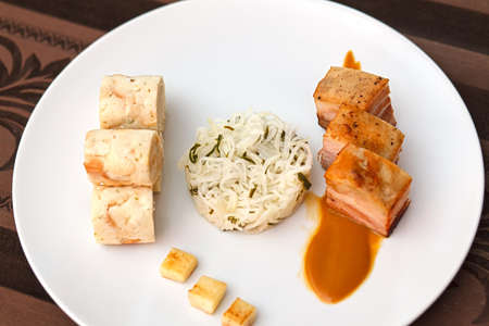 Pork belly with cabbage and bread dumplings. Beautifully arranged food on a white plate. Stock Photo