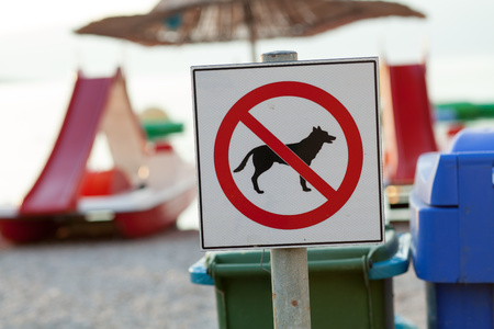 ordenanza: No entry.  Signs announcing the ban on dogs on the beach. (Shallow DOF)  Focus on brand blurred background.