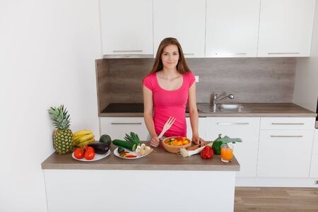 long-haired young woman prepares a modern, stylish kitchen healthy vegetable salad