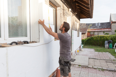 Man working with meter at thermal insulation of the facade.