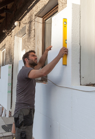 thermal insulation: Man working with level at thermal insulation of the facade.