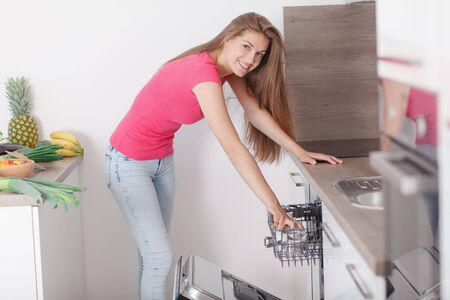 clearing dishwashers  Beautiful young woman performs household chores in the kitchen. Turns dishwasher in the modern interior of the new kitchen.