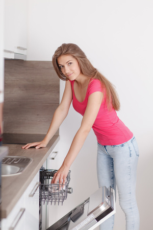 chores: clearing dishwashers  Beautiful young woman performs household chores in the kitchen. Turns dishwasher in the modern interior of the new kitchen.