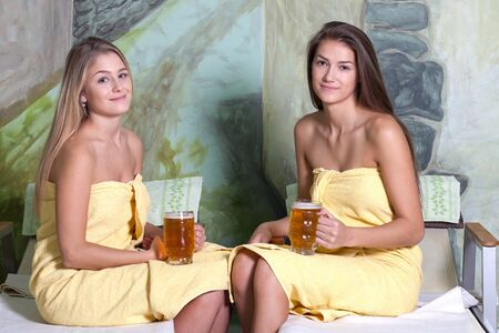 get together: Beautiful young girlfriends get together to use relaxation in the beer spa. Relax on a lounger after a massage with excellent beer.