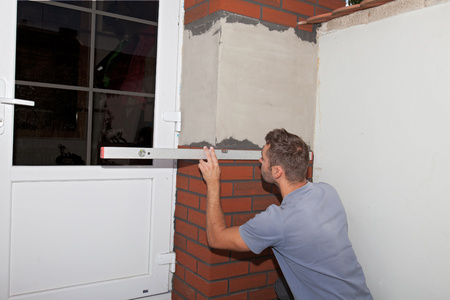 bubble level: Reconstruction of the house. Worker stuck brick cladding (imitation brick) on the outside facade. Plane measured with a bubble level. Stock Photo