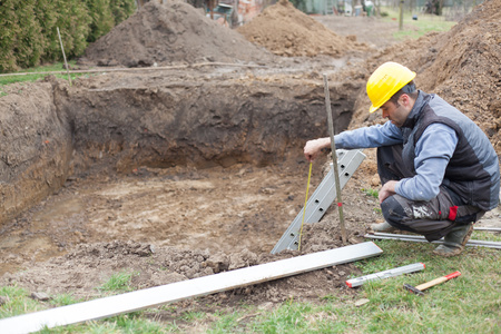 Man working on building a house with a private pool.