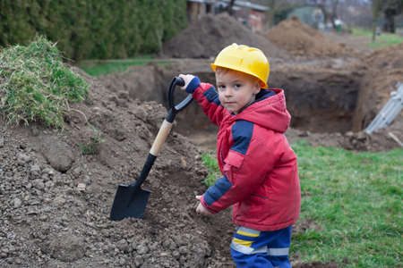 Little boy with a spade helps parents during the construction of the pool.
