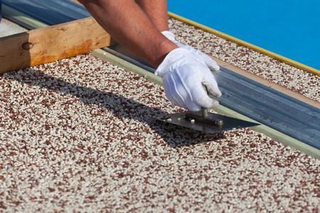 El trabajador coloca una alfombra de piedra con resina. (DOF superficial). Foto de archivo