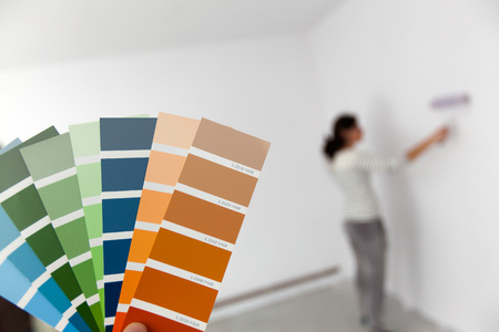 A young woman is looking at a color swatch for painting a room. (Shallow DOF)