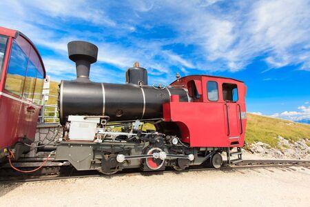 The steam train takes tourists on a mountain peak in the Austrian Alps (Salzburg, Schafberg).