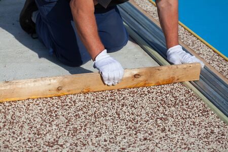 The worker places a stone carpet with resin. (Shallow DOF).