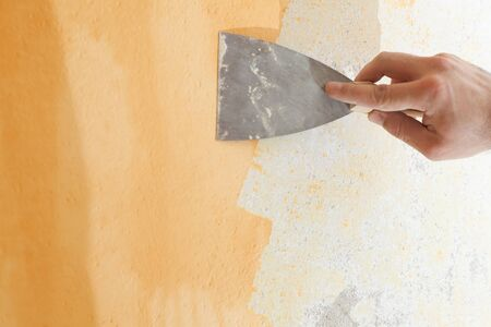 Scraping old plaster and applying new. Reconstruction of a new house.