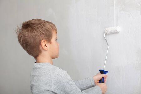 Little boy while painting the walls in the room.