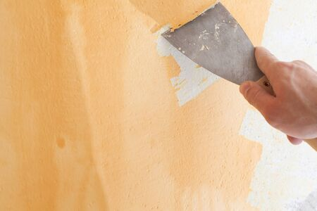 Scraping old plaster and applying new. Reconstruction of a new house. Archivio Fotografico - 146462693